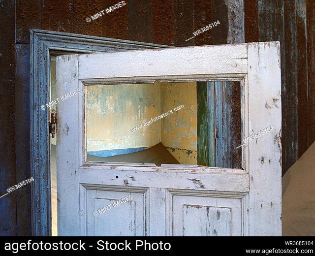 Open wooden door in a building buried in sand