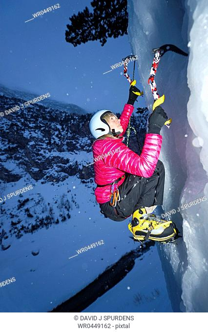 Women ice climbing at night on frozen waterfall hundreds of feet above the valley floor and river
