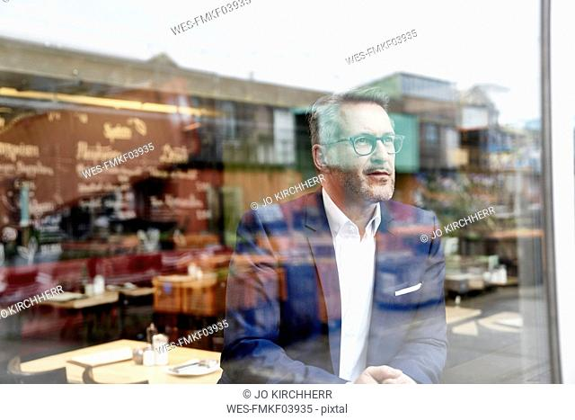 Confident mature businessman looking out of window