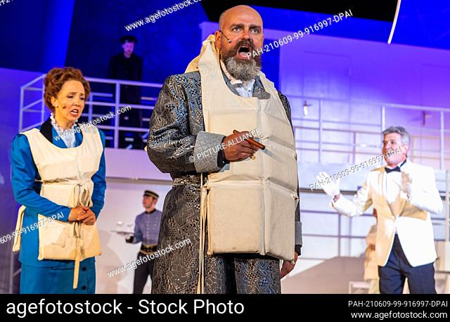 """07 June 2021, Mecklenburg-Western Pomerania, Schwerin: Stephan Brauer (in the foreground) sings the role of Benjamin Guggenheim in the musical """"""""Titanic"""""""" on..."""