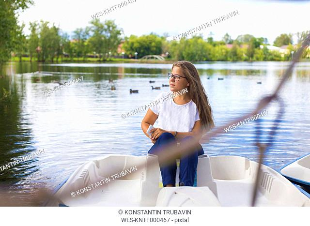 Russia, Tikhvin, teenager girl with smartphone, sitting in boat