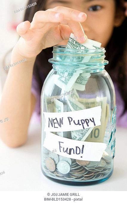 Vietnamese girl saving money in new puppy fund