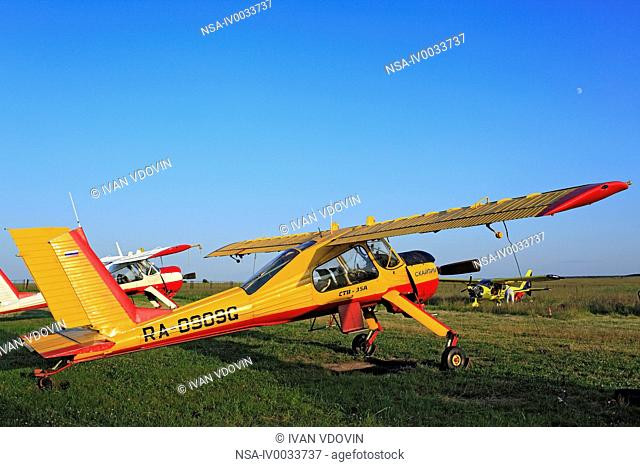 Light aircraft planes parked at a grass airfield, Russia