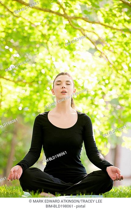 Caucasian woman practicing yoga in park