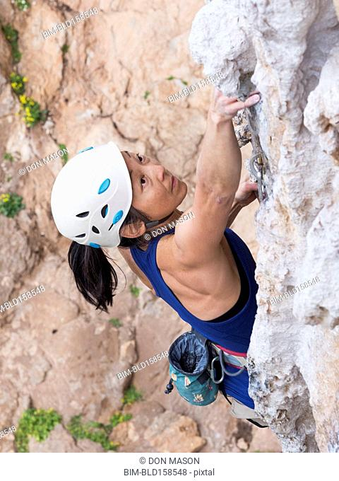 Japanese woman climbing rock wall