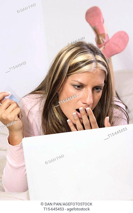 Woman in her 20's all dressed up with high heels shopping online in bed looking bored and tired