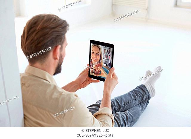 Young man sitting on floor talking to girlfriend on digital tablet video call