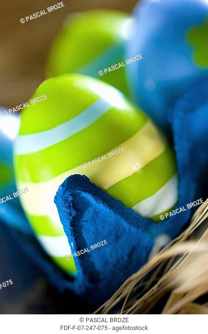 Close-up of three Easter eggs in an egg carton
