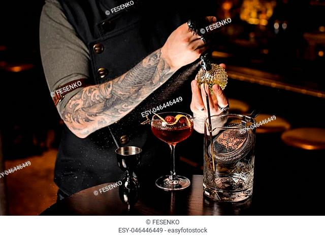 Professional bartender spraying on the delicious cocktail with a special liquid on the black table