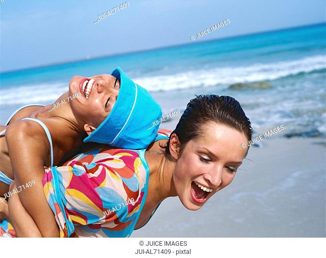 Portrait of two young women playing at the beach
