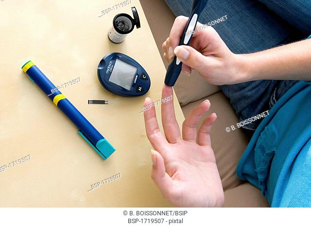 TEST FOR DIABETES Model. Woman using a lancet device to test her level of glycemia (diabetes). We can see the glucometer that will measure the rate of glucose...