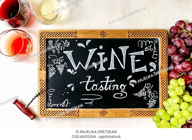 Variety of wine. Red, rose and white wine in old fashion glasses, corkscrew, bunches of grapes, chalkboard with handwritten chalk lettering Wine tasting