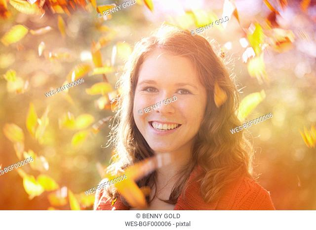 Portrait of happy young woman with swirling autumn leaves around her, close-up