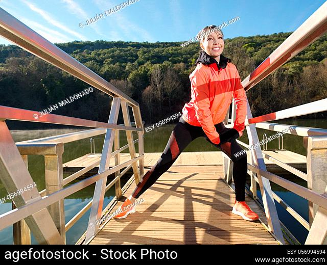 Young athlete woman exercises and stretches on the platform of a river