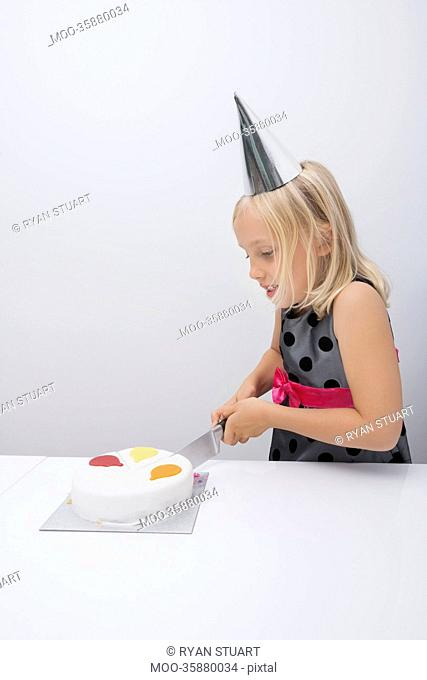 Cute girl cutting birthday cake at table in house