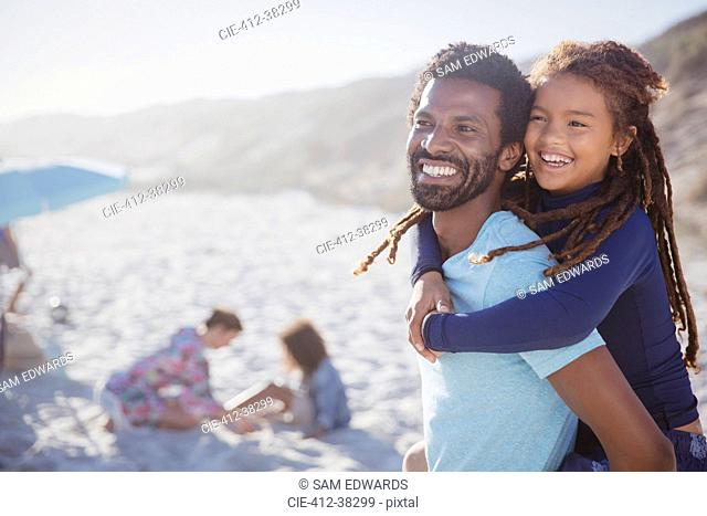 Smiling, affectionate father piggybacking daughter on sunny summer beach
