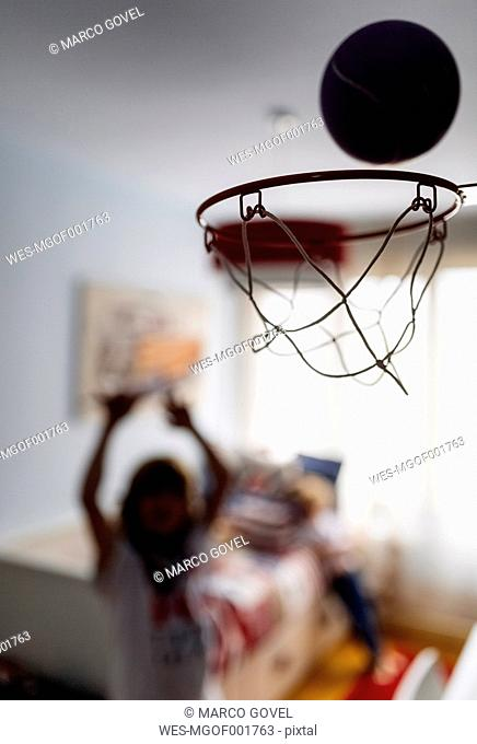 Boy throwing ball into hoop at children's room