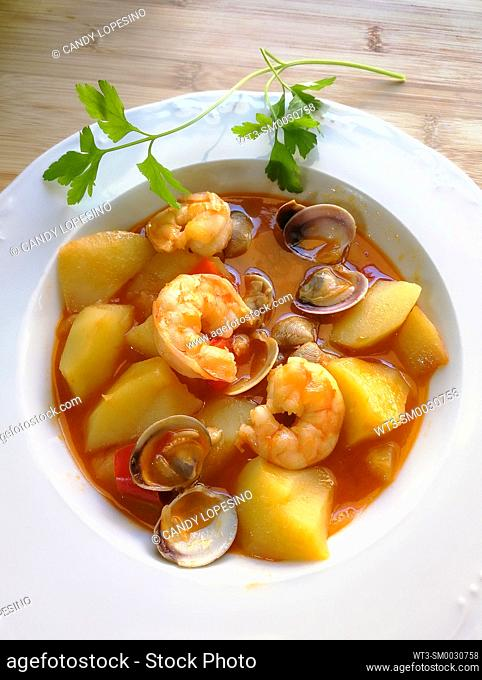Potatoes a la marinera with prawns and clams in a white porcelain plate and parsley branch