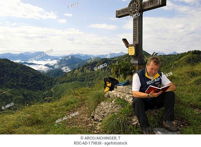 Wanderer at summit cross of mountain Burgspitz, 1429 m, national park Limestone Alps, Upper Austria, Austria