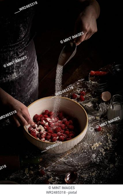 Valentine's Day baking, woman preparing fresh raspberries in a bowl, adding sugar