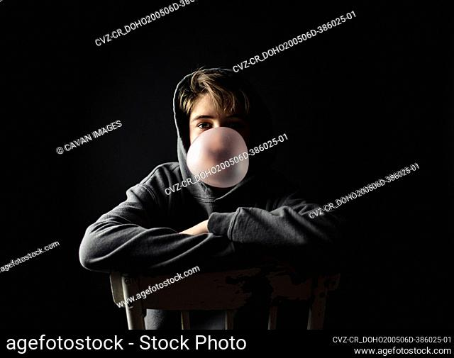 Teen boy in hoodie sitting on a chair in dark room blowing a bubble