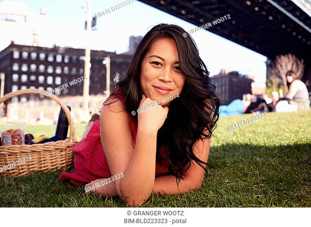 Pacific Islander woman laying on grass with picnic basket
