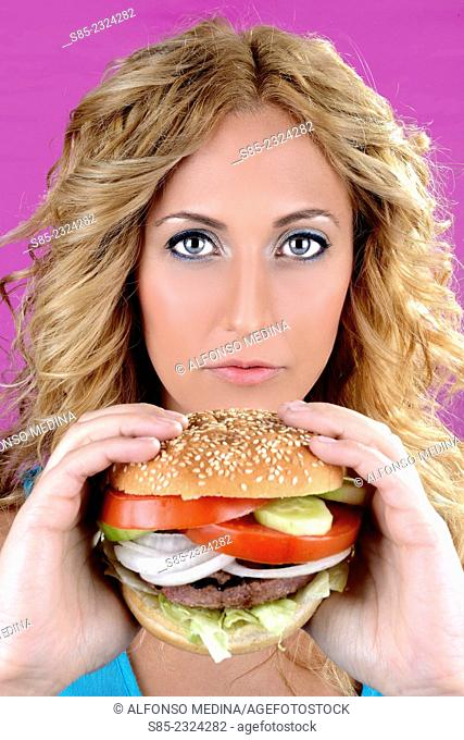 Blond young girl holding a burger