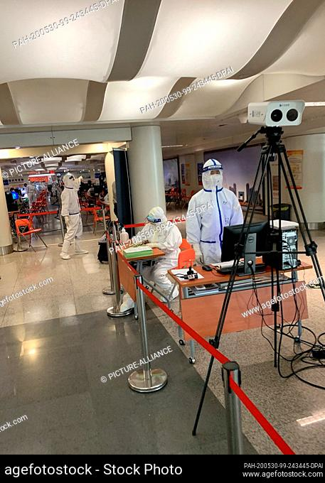 29 May 2020, China, Tianjin: At Tianjin airport, officials wearing Covid-19 protective suits and face visors are behind a device that measures the body...