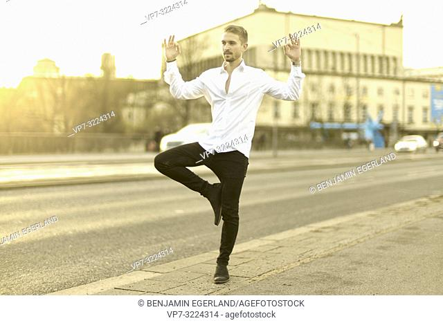 calm relaxed young man balancing on one foot at street, meditating, in Munich, Germany