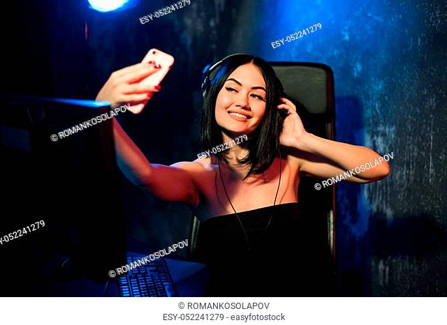 Cheerful gamer streamer girl wearing headset and sitting near her pc computer taking selfie on the phone during online game