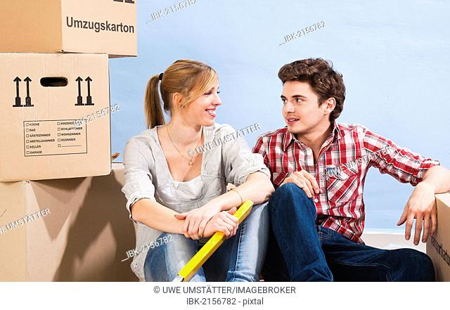 Young couple sitting between packing boxes