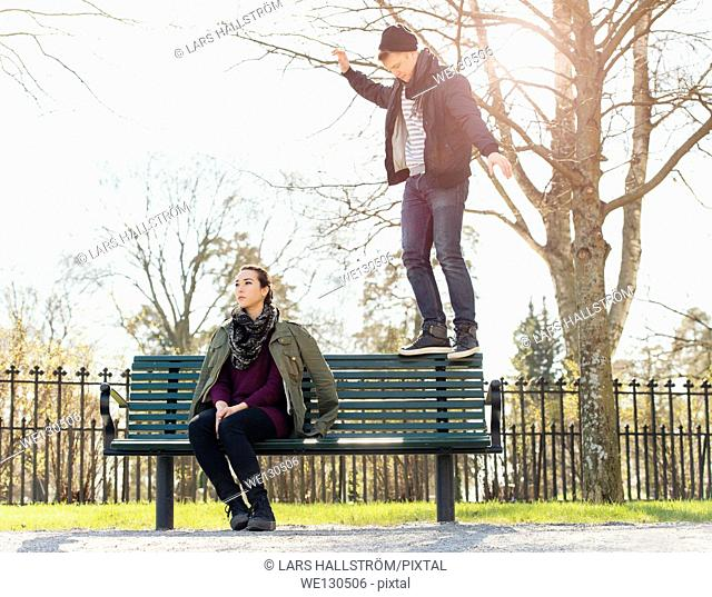 Young man trying to impress indifferent girl by balancing on a park bench