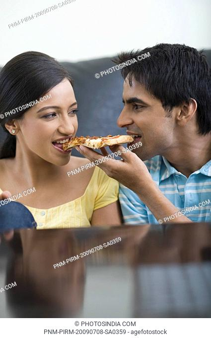 Close-up of a couple eating a slice of pizza