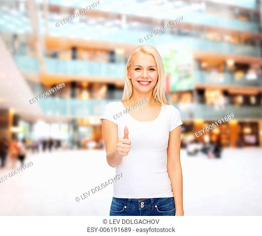 t-shirt design and happy people concept - woman in blank white t-shirt showing thumbs up