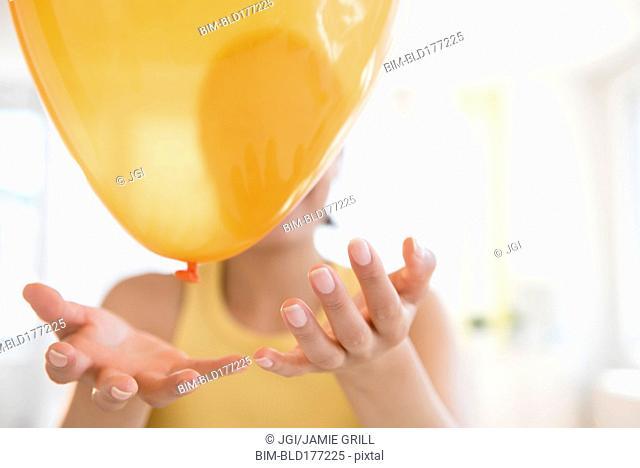 Hispanic woman playing with balloon