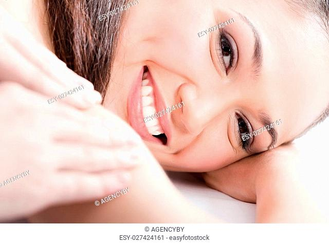 Smiling woman receives body massage at spa salon