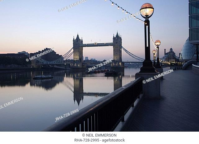 Tower Bridge reflected in the calm water of the River Thames in the early morning, viewed from the South Bank, London, England, United Kingdom, Europe
