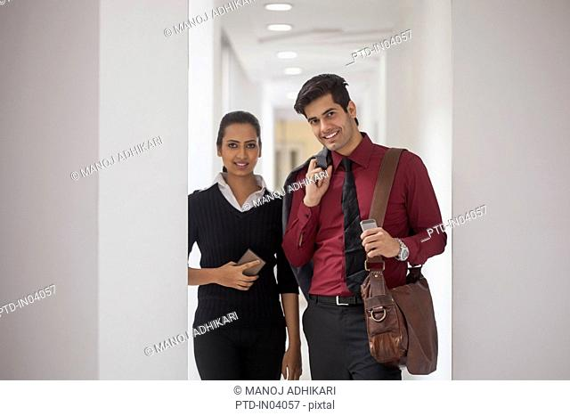 India, Two business people standing in corridor