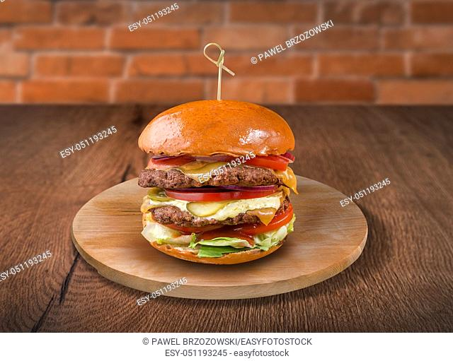 Hamburger on wooden background. For fast food restaurant design or fast food menu
