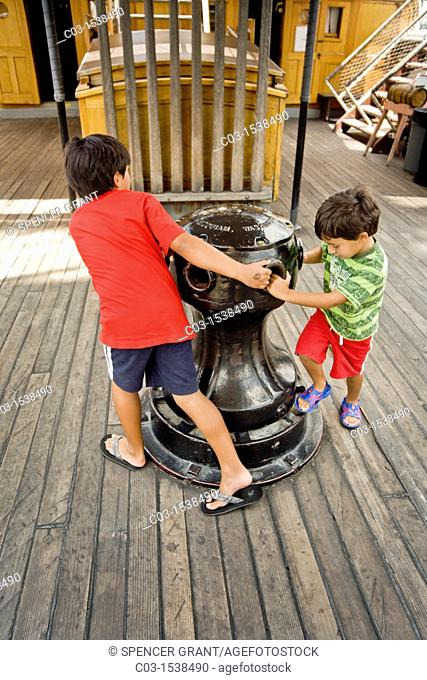 Two boys play around the capstan of the sailing ship Star of India at the San Diego Maritime Museum
