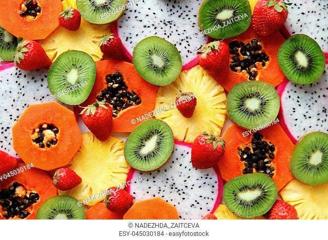 Mixed ripe and fresh fruits and berries close up for background. Dragon fruit, pineapple, papaya, kiwi, strawberry