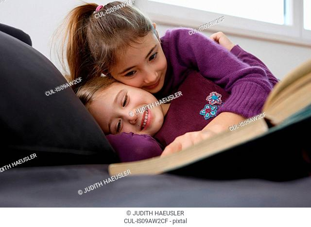Surface level view of girl lying down on sofa reading book, hugging and smiling