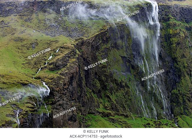 High winds whip waterfalls up the steep cliffs in southern Iceland, Europe