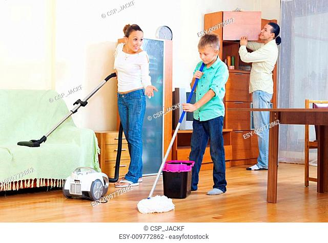family of three with teenager doing housework