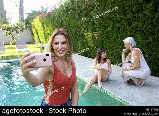Sisters meeting in an afternoon by the pool in the country house located in the surroundings of Seville