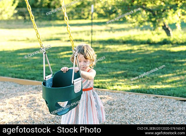 Little girl wanting to swing in the baby swing at a playground