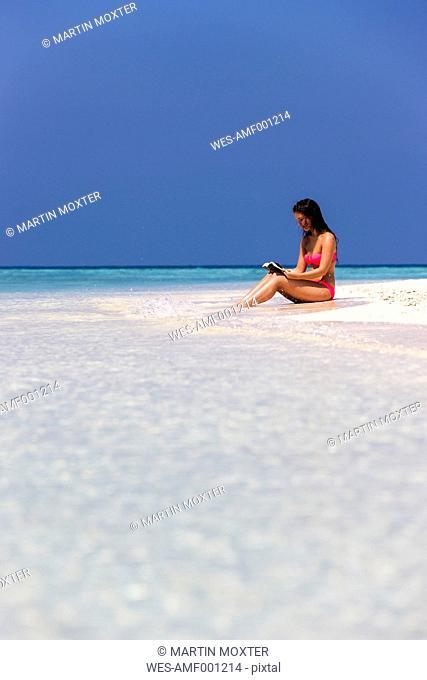 Maldives, Young woman in bikini sitting in shallow water reading book