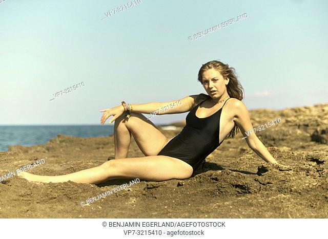 woman in one-piece swimsuit lying on rocks at beach, enjoying sunny weather and summer holiday in Crete, Greece