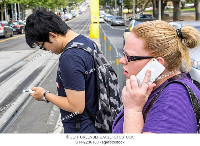 Australia, Victoria, Melbourne, Central Business District, CBD, La Trobe Street, tram, trolley, stop, City Circle Line, Asian, man, woman, smartphone, talking