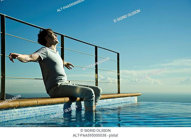 Man soaking feet in swimming pool